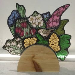 decorative stained glass piece featuring small robin amongst various wild flowers