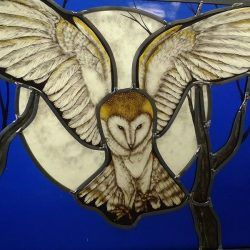 stained glass panel of owl with wings spread flying through trees moon in background