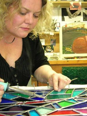 Daniella Lawson working on a stained glass project in the studio.